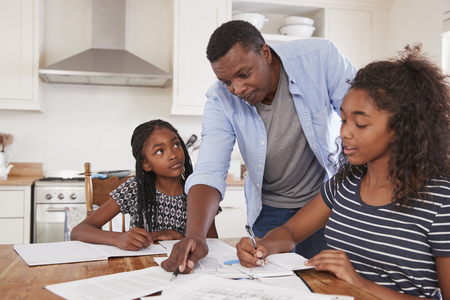 Father Helping Two Daughters Sitting At Table Doing Homework Imagens