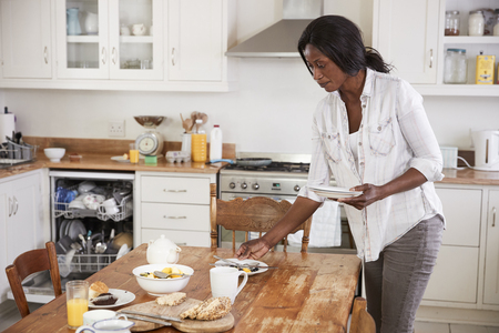 Woman Clearing Breakfast Table And Loading Dishwasher