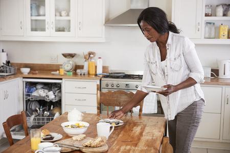 Vrouw die Ontbijtlijst opruimt en Vaatwasmachine laadt