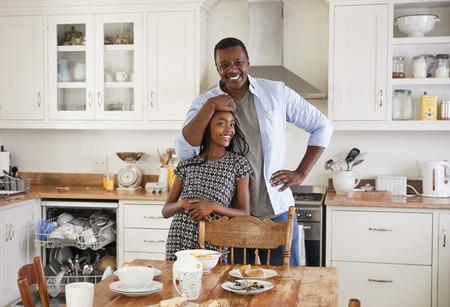 Dochter die Vader helpt om Lijst na Familiemaaltijd te ontruimen Stockfoto