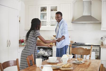 Figlia aiutare padre a tavola chiaro dopo pasto della famiglia