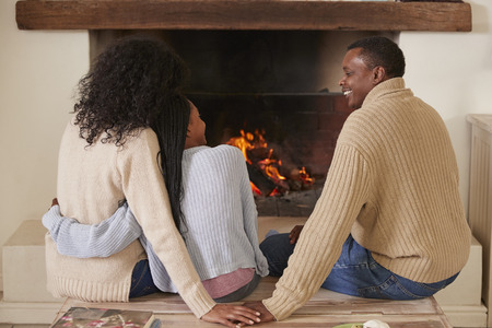 Parents Sitting With Daughter In Lounge Next To Open Fire