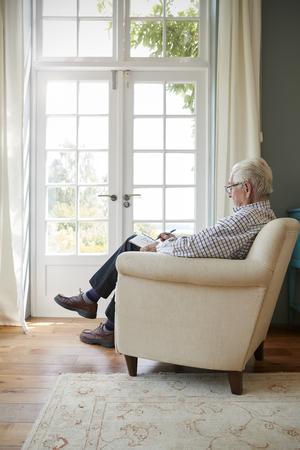 Senior man sitting in armchair doing  crossword