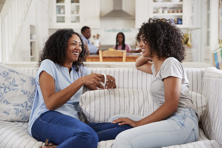 Mother Talking With Teenage Daughter On Sofa