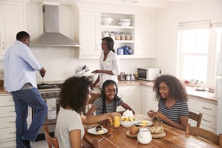 Famiglia con i bambini adolescenti che mangiano la prima colazione in cucina Archivio Fotografico - 88062908