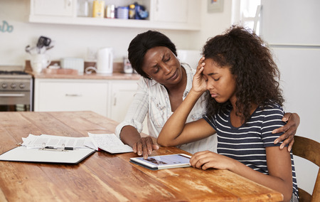 Mother Helps Stressed Teenage Daughter With Homework Stockfoto