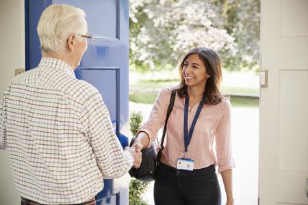 年配の男性挨拶の若い女性が家庭訪問を行う