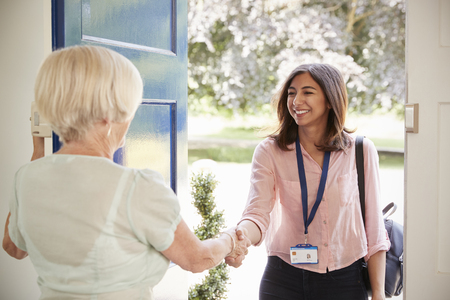 Senior woman greeting female care worker making home visit