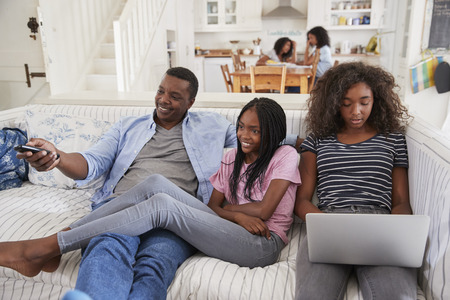Father Sitting On Sofa Watching TV With Teenage Daughters Foto de archivo
