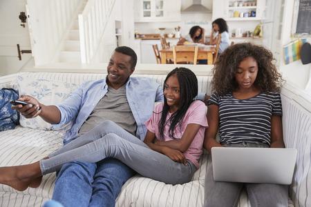 Vader zittend op de bank tv-kijken met tienerdochters