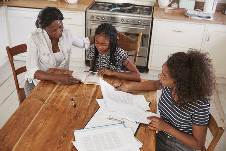Mother Helping Two Daughters Sitting At Table Doing Homework Stock Photo