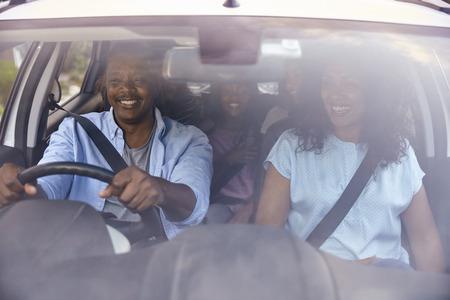 Familie met tienerkinderen in auto op wegreis