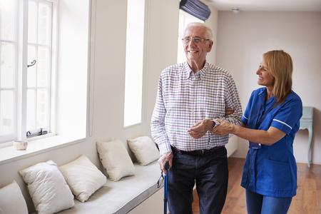 수석 남자가 지팡이를 사용하여 걷는 것을 돕는 간호사