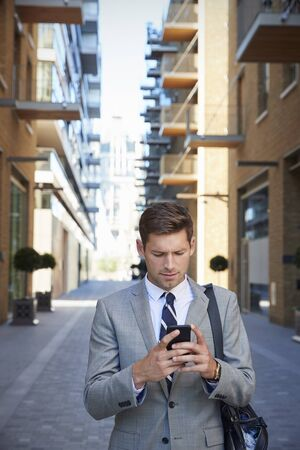 Businessman Walking To Work In City Looking At Mobile Phone