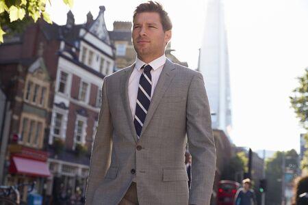 Businessman Walking To Work Along City Street Banco de Imagens