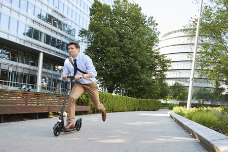 Young Businessman Commuting To Work Through City On Scooter Фото со стока