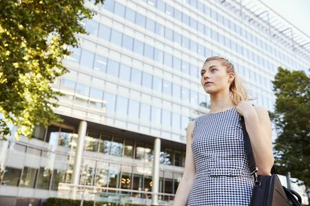 Businesswoman Walking Past Modern City Offices On Way To Work