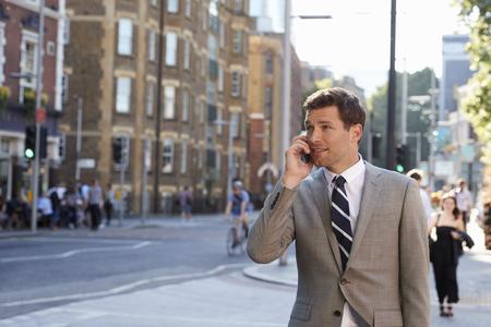 Businessman Talking On Mobile Phone Walking Along City Street