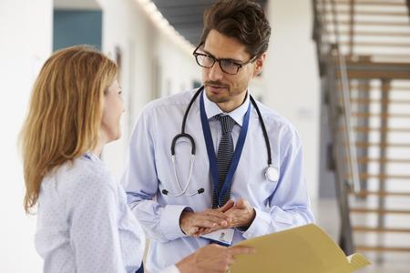 Jonge mannelijke en vrouwelijke artsen die elkaar raadplegen