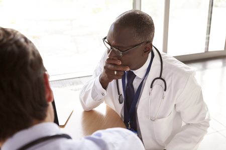 Two senior healthcare workers in consultation, over shoulder Imagens