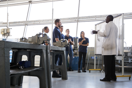 Engineering apprentices stand at a training presentation, low angle Stock Photo