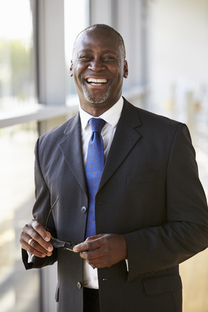 Portrait of a smiling businessman holding glasses Stock Photo