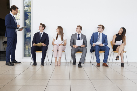 Recruiter and people waiting for job interviews, full length Stock Photo