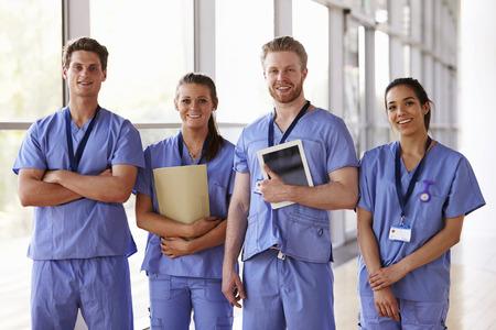Group portrait of healthcare workers in hospital corridor