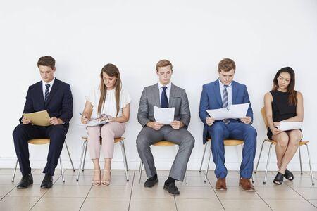 Les candidats en attente d'entrevue d'emploi, pleine longueur, devant
