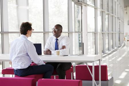 ビジネスミーティング中に2人のビジネスマンが話す