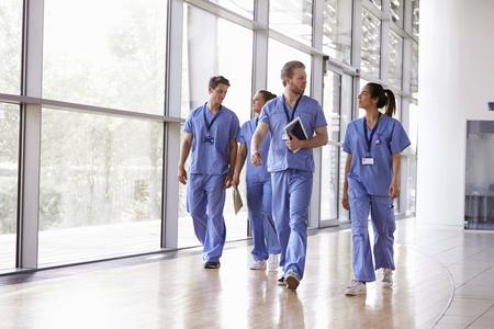 Vier Gesundheitshelfer scheuert herein, gehend in Korridor Standard-Bild - 89639891