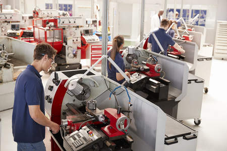Trainee engineers operating equipment in a small factory Stock Photo - 89639899