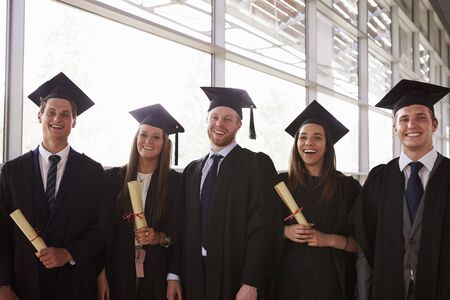 Five graduates in mortars and gowns holding certificates