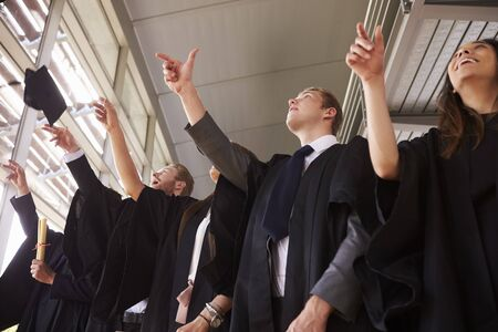 Graduates in gowns throwing their mortar boards in the air