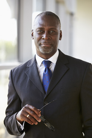 Portrait of a businessman holding glasses looking to camera