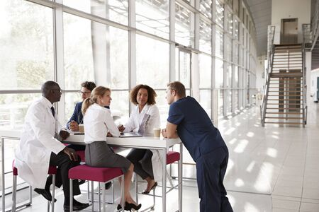 Five healthcare workers at a table in modern hospital lobby