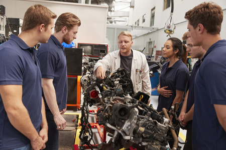 Mechanic showing parts of an engine to apprentices, close up Banque d'images