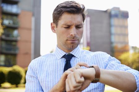 Businessman Walking Through City Park Looking At Smart Watch