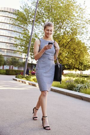 Businesswoman Walking To Work In City Looking At Mobile Phone Stock Photo