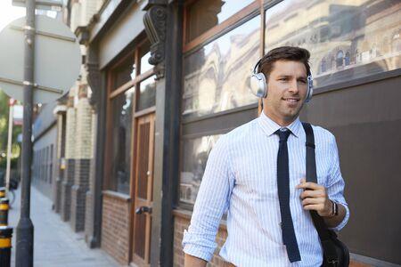Businessman Wearing Wireless Headphones Walking To Work