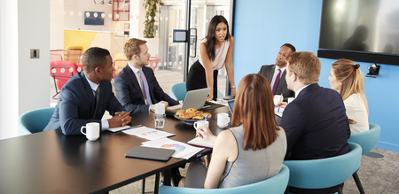 Female manager stands addressing colleagues in meeting room Stock Photo