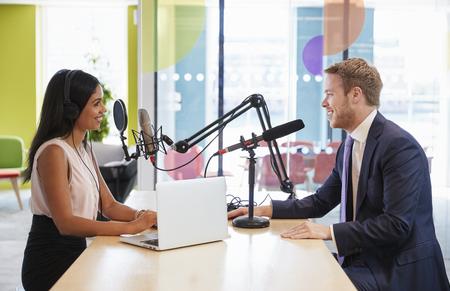 Junge Frau, die einen Gast in einem Studio für einen Podcast interviewt Standard-Bild