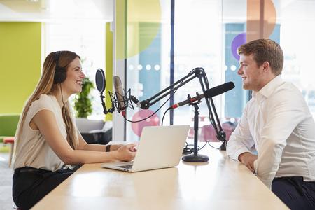 若い女性は、ポッドキャストのためのスタジオでゲストのインタビュー