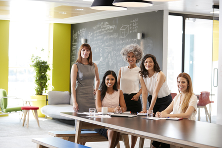 Five female colleagues at a work meeting smiling to camera Stock Photo