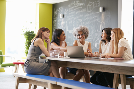 Female work colleagues using laptop in an informal meeting Stock Photo - 89290371