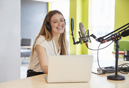 Mujer joven feliz transmitiendo en un estudio, primer plano Foto de archivo - 89290379