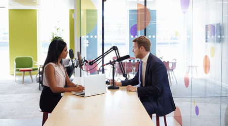 Young woman interviewing a guest in a studio for a podcast Stock Photo
