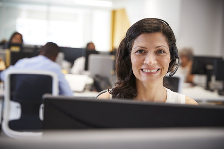 Middle aged woman working at computer with headset in office Stock Photo