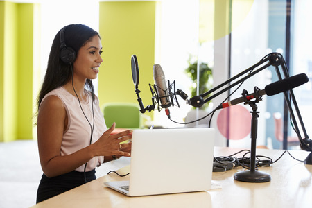 Young mixed race woman recording a podcast in a studio Stock Photo