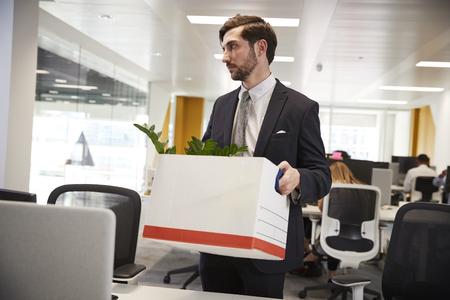 Fired male employee holding box of belongings in an office Фото со стока
